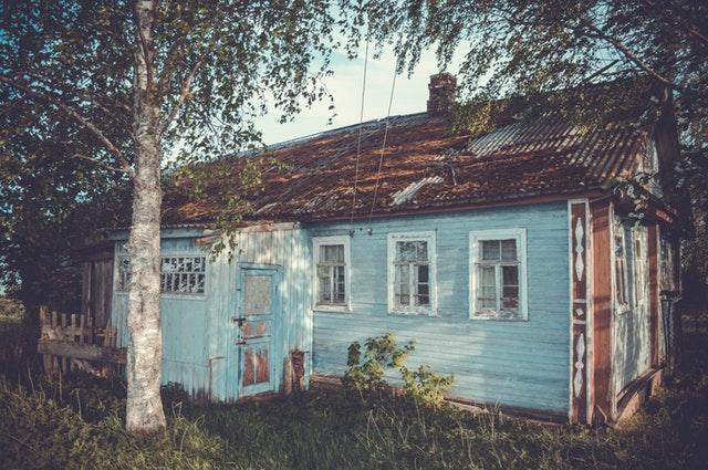 Stará, drevená modrá chata uprostred lesa.jpg