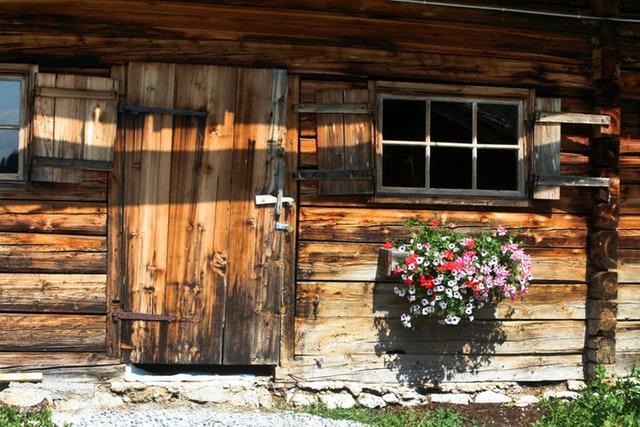 Drevená chata so starým oknom, veľkými dverami a muškátmi na stene.jpg