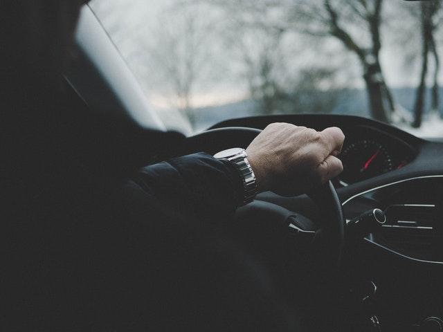 Muž v čiernej bunde šoféruje auto.jpg