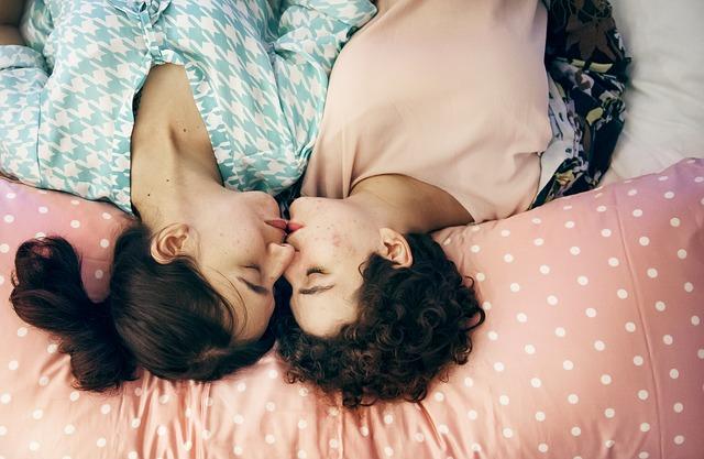 Dve ženy ležia vedľa seba v posteli a bozkávajú sa.jpg