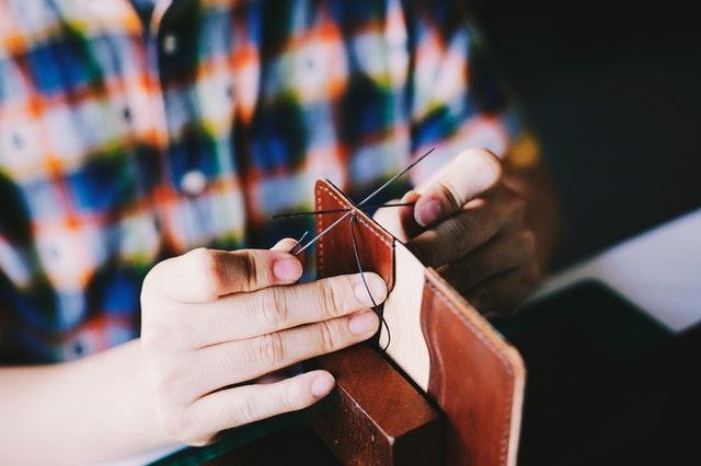 Muž šije koženú peňaženku