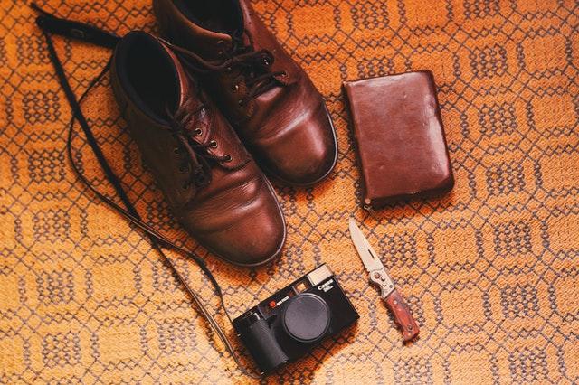 Kožené topánky, nôž a peňaženka na zemi